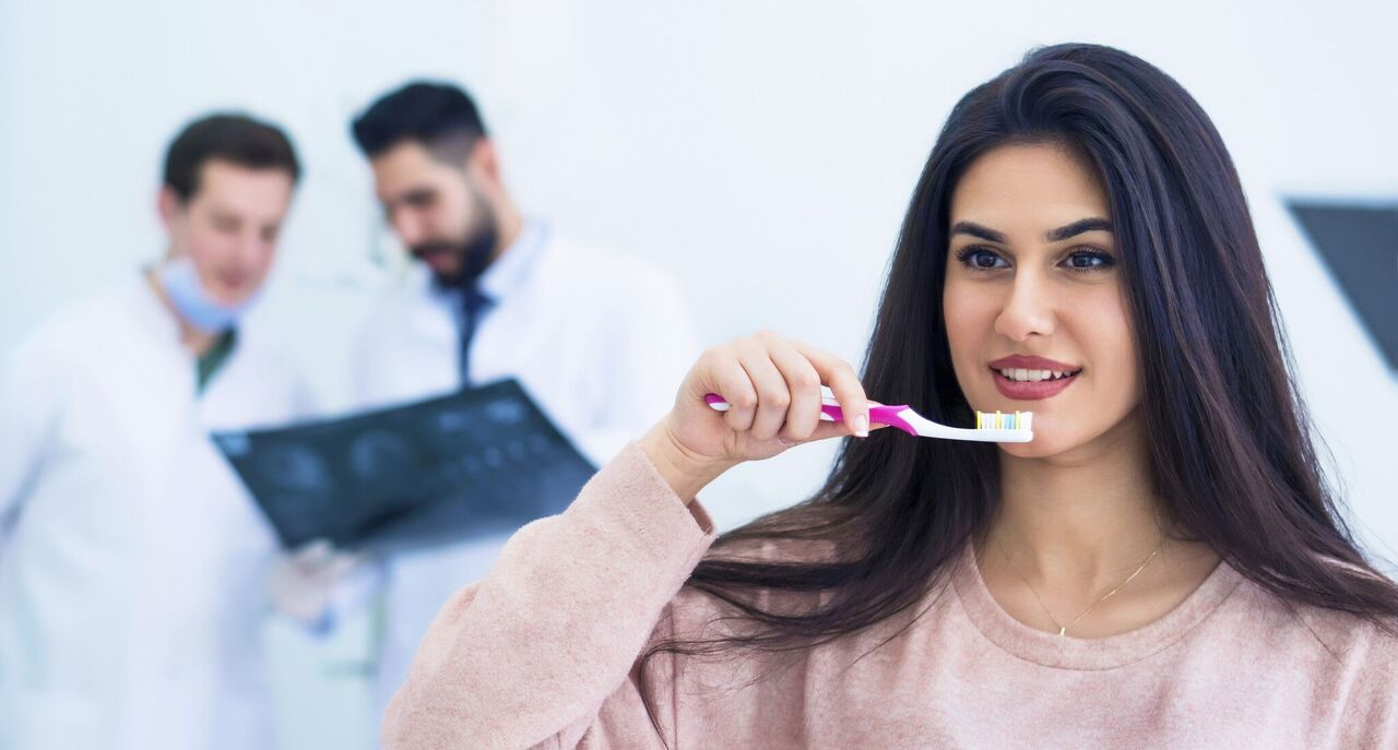 Rosenthal Dark Haired Woman Brushing Teeth Alongside Dentists