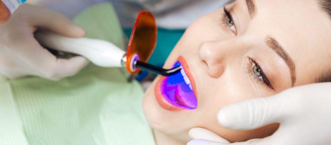 Rosenthal Family Dentistry - Woman doing laser whitening